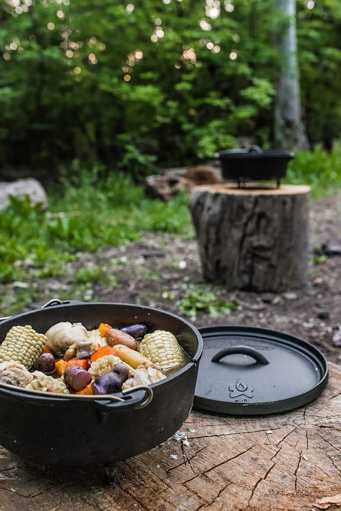 close up of dutch oven filled with stew on a tree stump with another dutch oven in the distance