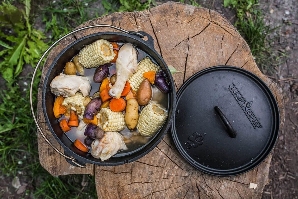 A dutch oven full of chicken drumsticks, potatoes, and corn