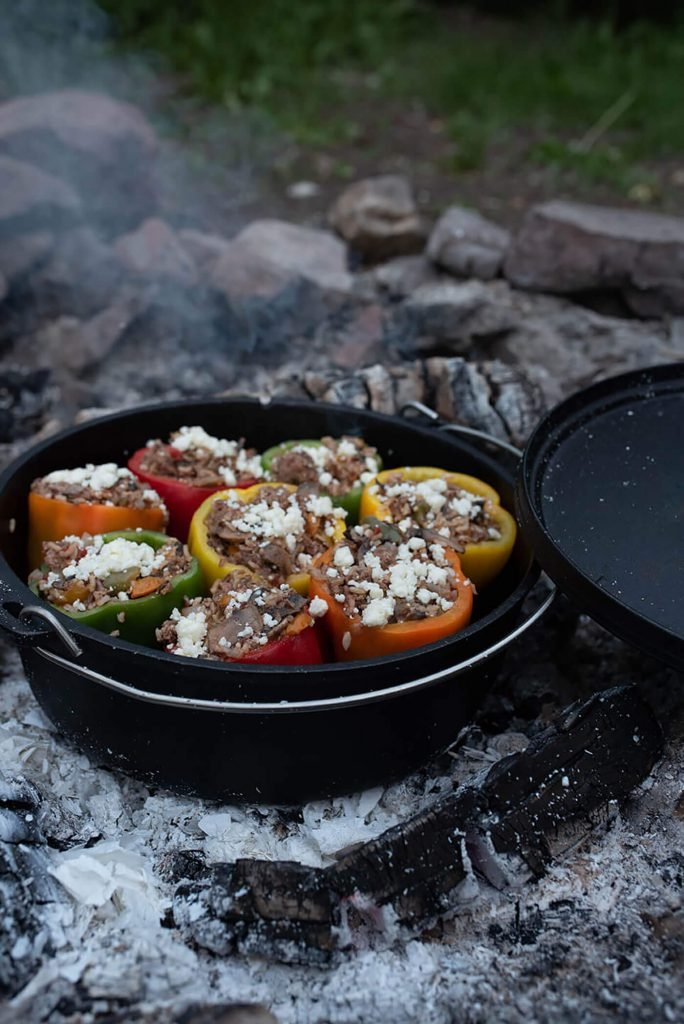 Stuffed Peppers roasting in a dutch oven on a campfire